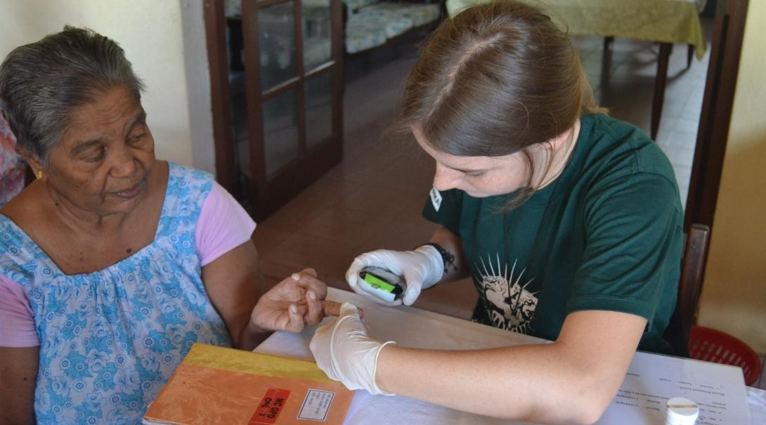 A Sri Lankan woman has her blood sugar levels checked by a student on a short-term volunteer trip overseas.
